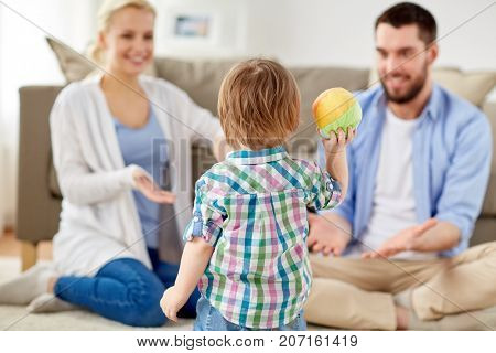 family and people concept - happy little son and parents playing with ball at home