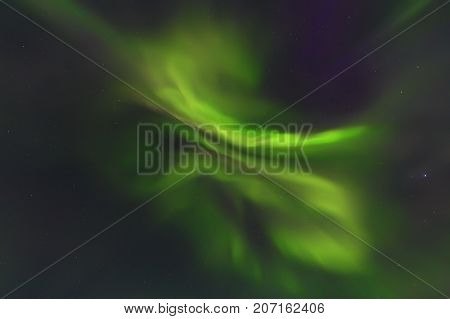 Bright aurora borealis in night starry sky. Northern lights background.
