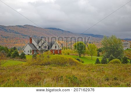 Vermont Fall Foliage in a cloudy day, Mount Mansfield in the background, Vermont, USA.