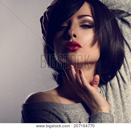 Sexy Makeup Woman With Short Bob Hair Style, Red Lipstick Touching Her Face On Dark Shadow Backgroun