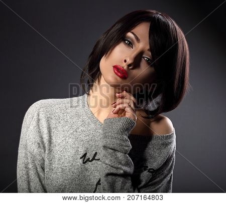 Sexy Beautiful Makeup Woman With Short Bob Hair Style, Red Lipstick Touching Her Face On Dark Shadow