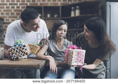A Sad Girl Sits On A Chair, And A Cheerful Man And Woman Chew Her With Gifts For Her