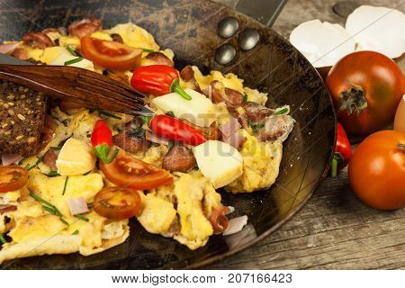 Fresh scrambled egg with ham and chilli peppers on a steel pan. A nourishing traditional breakfast. Calorie meals