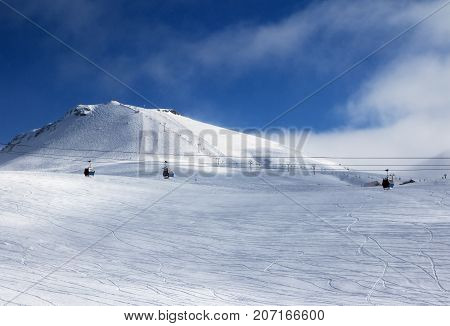 Gondola And Chair Lifts On Ski Resort At Winter Evening With Snowfall