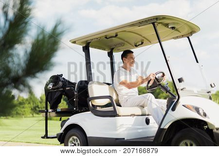 Smiling Man Riding A White Golf Cart