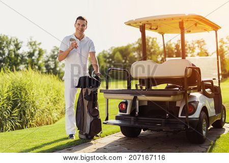 A Smiling Man In A White Suit Stands Holding A Golf Club Next To A Golf Cart