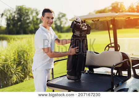 A Man In A White Suit Is Holding A Bag With Golf Clubs, Which Stands In The Trunk Of The Golf Court