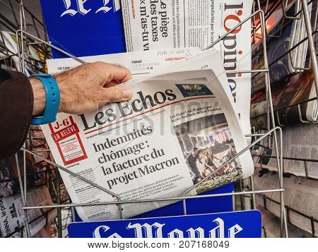 PARIS FRANCE - OCT 3 2017: Man buying newspaper with news from Spain about the Catalonia Referendum and protests