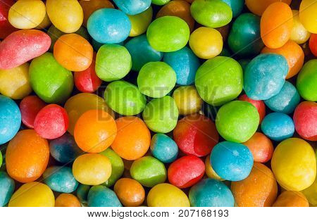 Happy colored sweets background. Many candy confection small green, yellow, red drops. Bright texture and round forms of raisins or nuts in sugar.