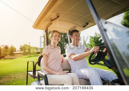 A Couple Is Going To Play Golf. A Man Sits Behind The Wheel Of A White Golf Car, A Woman Sits Near