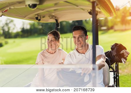 A Great Day For Golf. A Couple Is Sitting In A White Golf Cart. On The Trunk Lies A Bag With Golf Cl