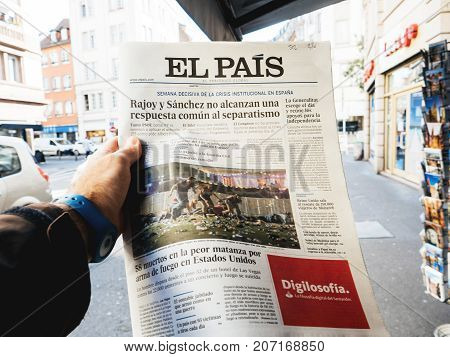 PARIS FRANCE - OCT 3 2017: Man buying Spanish El Pais newspaper with socking title and photo at press kiosk about the 2017 Las Vegas Strip shooting in United States with about 60 fatalities and 527 injuries