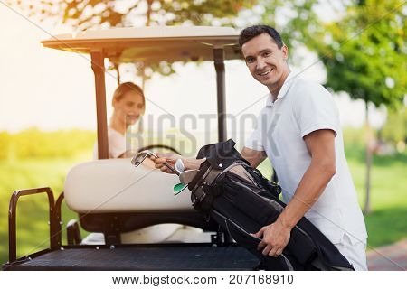 A Woman Is Driving A Golf Car. A Man In The Foreground Stands Next To The Trunk And Pulls Out A Golf