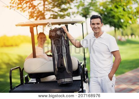 A Woman Sits Behind The Wheel Of A Golf Cart, A Man Stands In The Foreground And Holds A Bag With Go