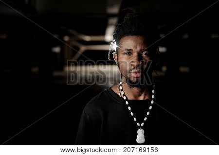 Close up portrait of dark skinned man dressed in black clothes on the dark background