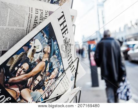 PARIS FRANCE - OCT 3 2017: Pedestrians near the Times newspaper with socking title and photo at press kiosk about the 2017 Las Vegas Strip shooting in United States with about 60 fatalities and 527 injuries