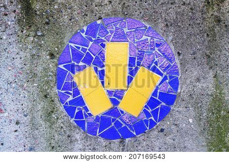 Mosaic tiles of blue color on a concrete wall street