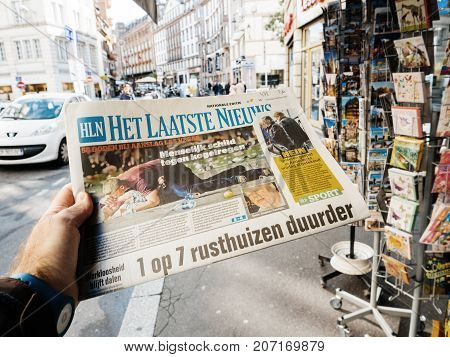 PARIS FRANCE - OCT 3 2017: Man buying het laatste nieuws newspaper with socking title and photo at press kiosk about the 2017 Las Vegas Strip shooting in United States with about 60 fatalities and 527 injuries