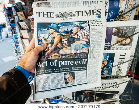 PARIS FRANCE - OCT 3 2017: Man buying The Times newspaper with socking title and photo at press kiosk about the 2017 Las Vegas Strip shooting in United States with about 60 fatalities and 527 injuries