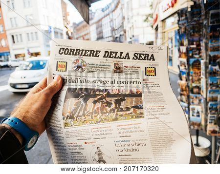 PARIS FRANCE - OCT 3 2017: Man buying Corriere della Sera newspaper with socking title and photo at press kiosk about the 2017 Las Vegas Strip shooting in United States with about 60 fatalities and 527 injuries
