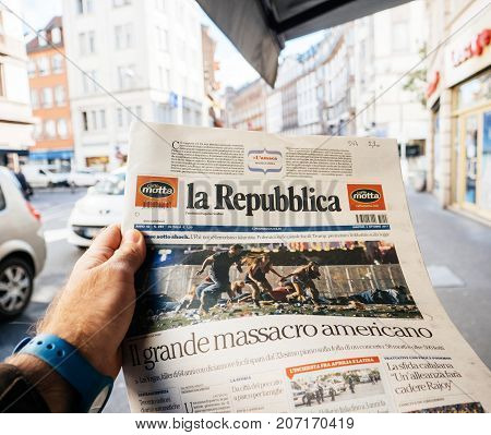 PARIS FRANCE - OCT 3 2017: Man buying Italian La Repubblica newspaper with socking title and photo at press kiosk about the 2017 Las Vegas Strip shooting in United States with about 60 fatalities and 527 injuries