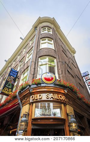 AMSTERDAM NETHERLANDS - JUNE 21 2016: Vertical picture of the facade of the famous Old Sailor Pub located in the Red Light District Amsterdam in a sunny day with clouds. Amsterdam Netherlands.