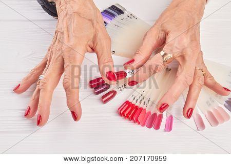 Old woman compares nail color with nail sample. Senior woman hands with red manicure holding red nail polish sample. Woman in beauty salon.
