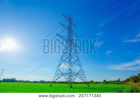High voltage post or High voltage tower in an agricultural landscape in the Thailand. In the background are the outbuildings of a farm