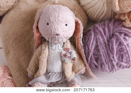 Cute handmade rabbit with wool close up. Plush vintage toy with materials of it, copy space. Creativity, handicraft, hobby concept