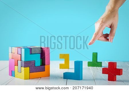 Concept of decision making process logical thinking. Logical tasks. Conundrum find the missing piece of the proposed. Hand holding wooden puzzle element. The hand indicates the right decision.