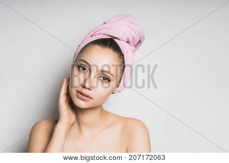 a girl with a towel tied around her head, puts on her makeup