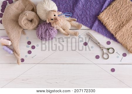 Handmade toy making, artisan workplace top view background. Bear and materials for creating vintage plaything, home workshop, copy space for text