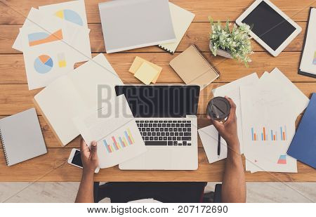 Office workspace top view. African-american businessman working at wooden desk, using laptop and various objects all around