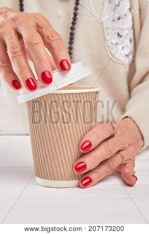 Woman hands is opening cardboard coffee cup. Female hands with red manicure opened take-out cup with cappuccino or latte.