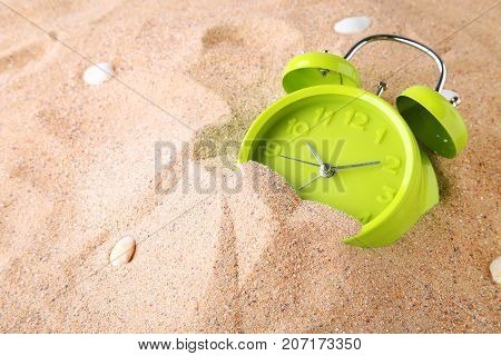 Green alarm clock on the beach sand
