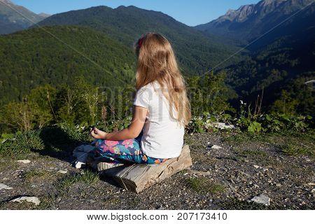 Little blonde girl meditating on top of mountain