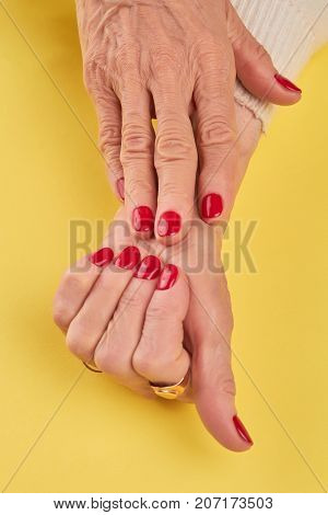 Old woman hands with red manicure. Female manicured hands on yellow background close up. Skin and nails spa and care.