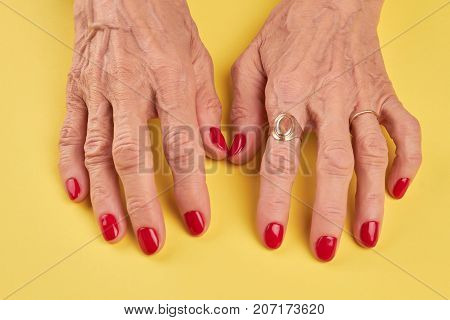 Elderly woman hands with red manicure. Senior woman hands with red nails on yellow background. Old woman hands with perfect red manicure.