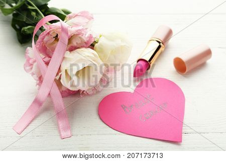 Pink ribbon with flowers pomade and inscription Breast Cancer on wooden table