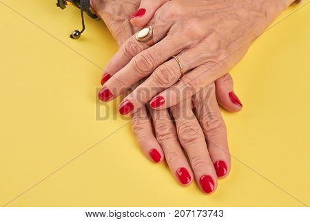 Female hands with beautiful red manicure. Senior woman hands with red nails polish on yellow salon table. Nail salon and spa.
