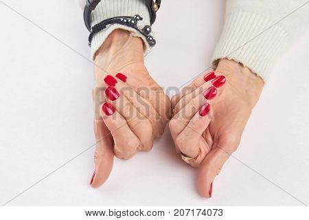 Woman hands with luxury red manicure. Elderly woman hands with beautiful red nails on white background. Salon beauty and spa.