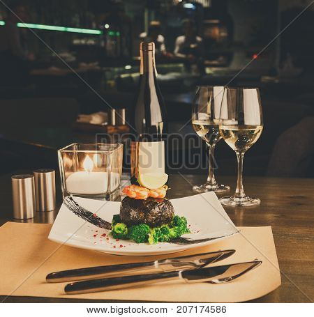 Wining and dining at restaurant. Dorado fillet wrapped in nori on steamed broccoli with shrimps and lemon piece. Table served with wine and fine cutlery for luxurious dinner. Gourmet cuisine meals