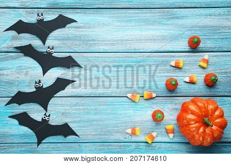 Halloween candies with black bats on blue wooden table
