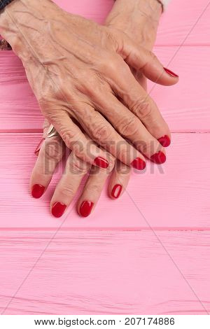 Female manicured hands on wooden background. Senior woman hands with beautiful red manicure on pink wooden background. Nail salon and spa.