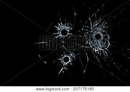 three bullet holes in glass closeup on black background