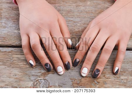 Manicured hands on old wooden background. Young woman hands with modern manicure on vintage wooden background. Salon beauty and spa.