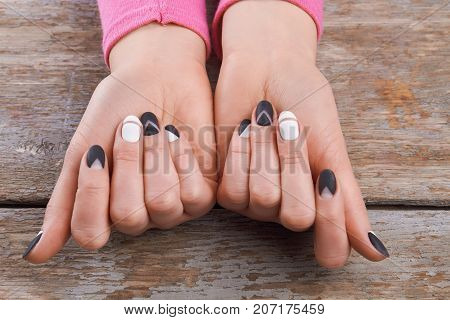 Well-groomed hands with cute manicure. Beautiful woman hands with black and white designed nails on old wooden background. Fashion female manicure design.