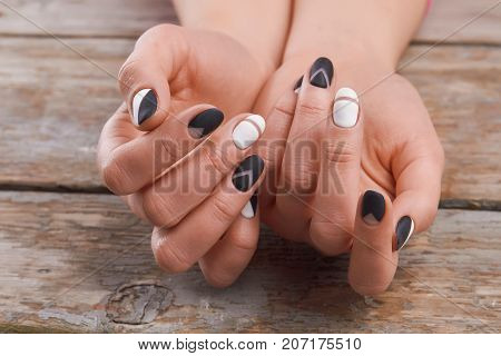 Cute manicure on female hands. Woman hands with black and white design manicure on vintage wooden background. Nails and skin treatment. Matte manicure on female hands.