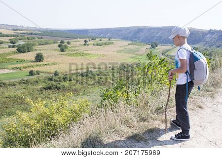 Small foot tourist. The boy dressed of black trousers , white t-shirt and cap with grey and blue backpack. Concept of travel in mountain. Child relying on a stick, staring into the distance.
