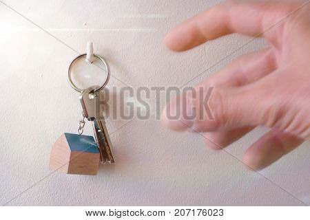 Hands Catching Keys On A Hook On The Wall